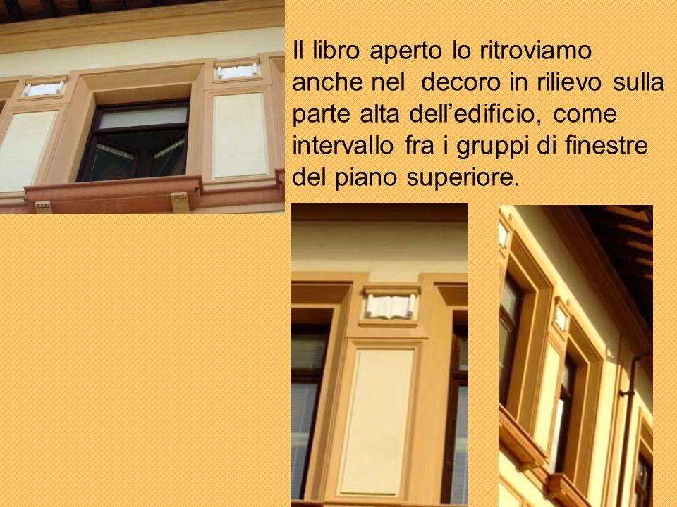 Il libro aperto lo ritroviamo anche nel decoro in rilievo sulla parte alta dell'edificio, come intervallo fra i gruppi di finestre del piano superiore.