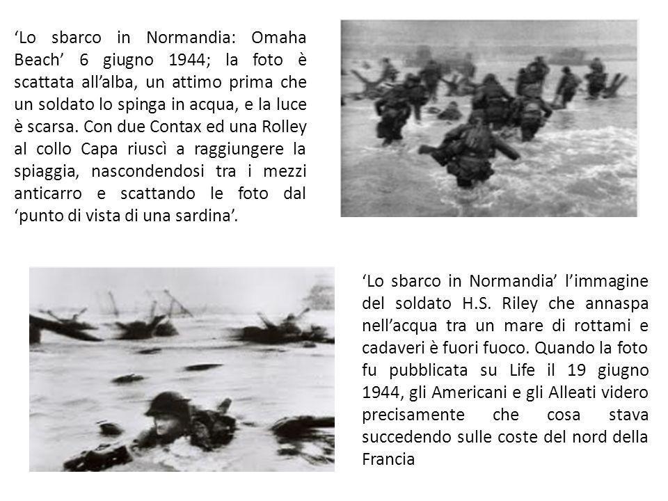 'Lo sbarco in Normandia: Omaha Beach' 6 giugno 1944; la foto è scattata all'alba, un attimo prima che un soldato lo spinga in acqua, e la luce è scarsa. Con due Contax ed una Rolley al collo Capa riuscì a raggiungere la spiaggia, nascondendosi tra i mezzi anticarro e scattando le foto dal 'punto di vista di una sardina'.