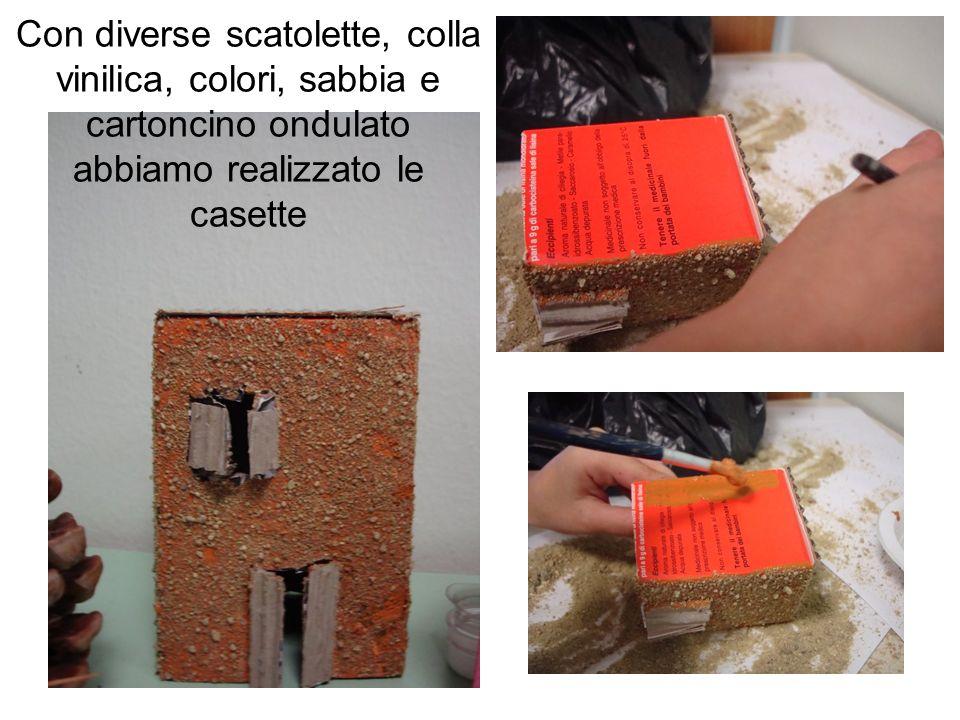 Con diverse scatolette, colla vinilica, colori, sabbia e cartoncino ondulato abbiamo realizzato le casette
