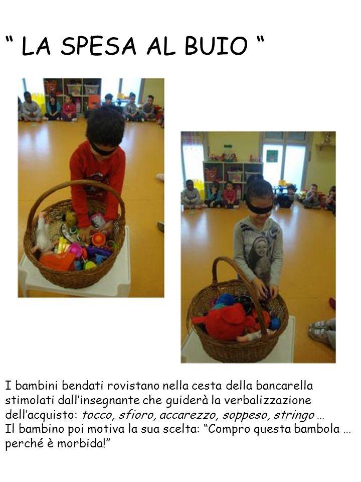 LA SPESA AL BUIO I bambini bendati rovistano nella cesta della bancarella.