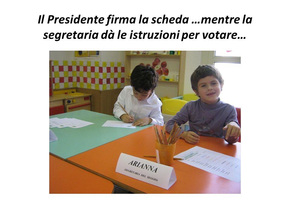 Il Presidente firma la scheda …mentre la segretaria dà le istruzioni per votare…