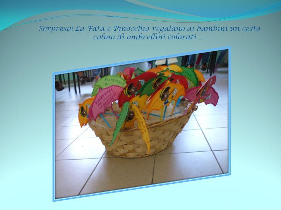 Sorpresa! La Fata e Pinocchio regalano ai bambini un cesto colmo di ombrellini colorati …