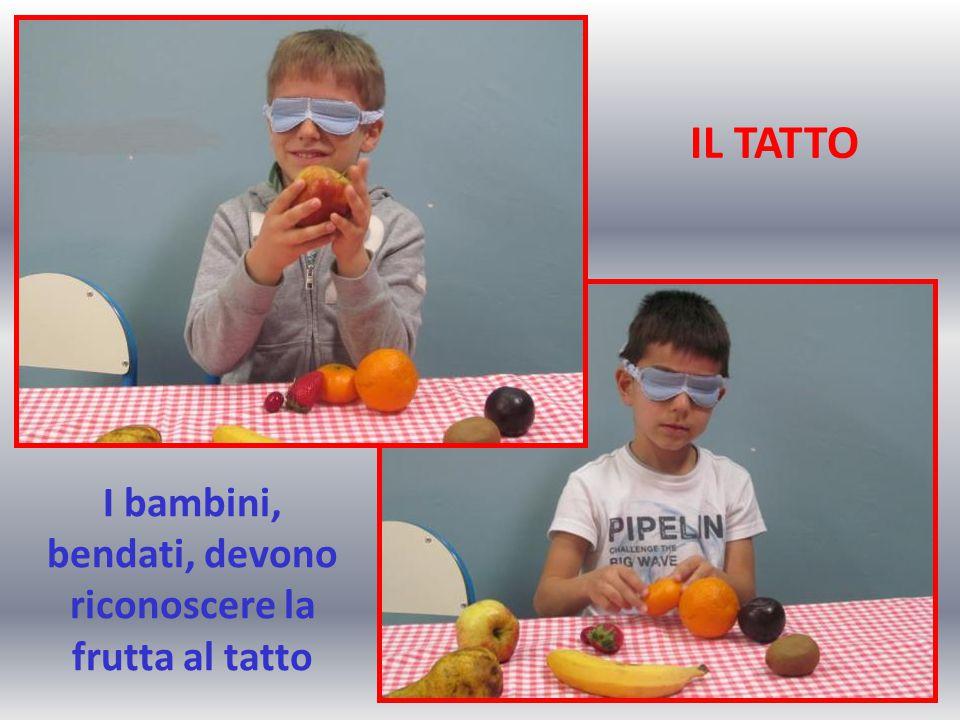 I bambini, bendati, devono riconoscere la frutta al tatto