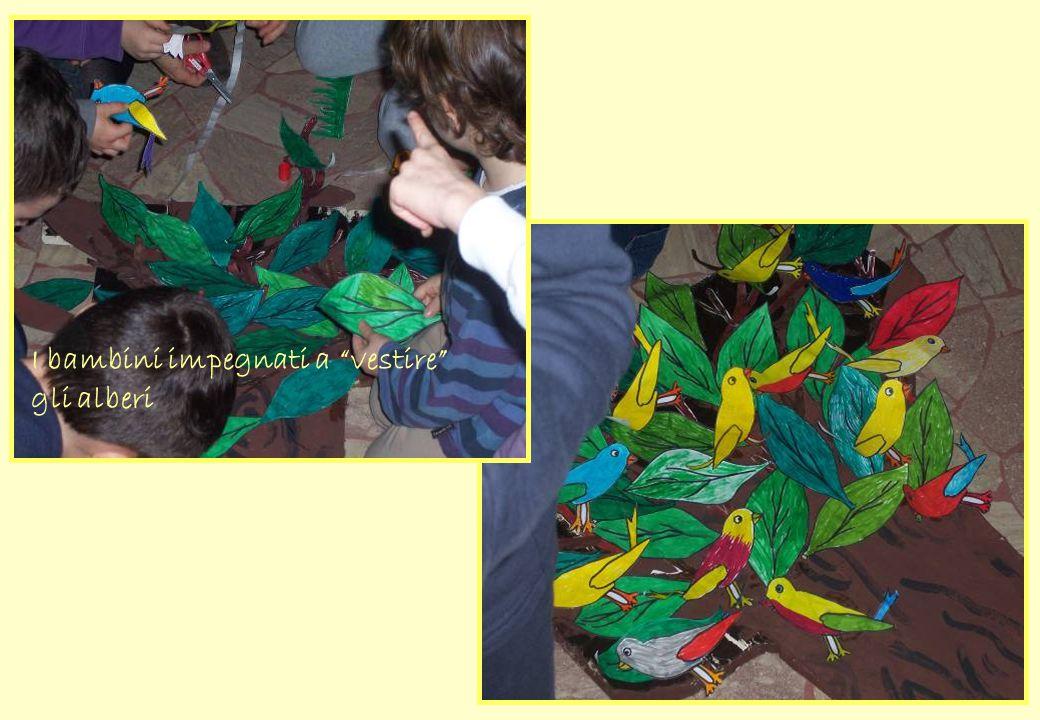 I bambini impegnati a vestire gli alberi