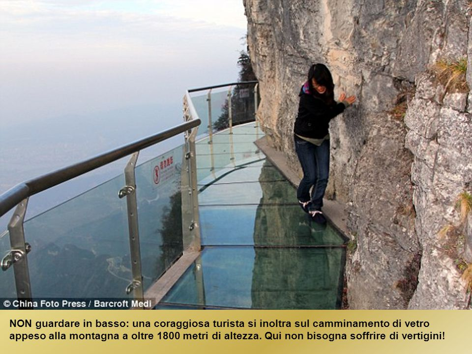 NON guardare in basso: una coraggiosa turista si inoltra sul camminamento di vetro appeso alla montagna a oltre 1800 metri di altezza.