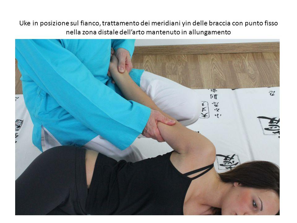 Uke in posizione sul fianco, trattamento dei meridiani yin delle braccia con punto fisso nella zona distale dell'arto mantenuto in allungamento