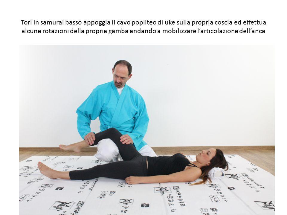 Tori in samurai basso appoggia il cavo popliteo di uke sulla propria coscia ed effettua alcune rotazioni della propria gamba andando a mobilizzare l'articolazione dell'anca