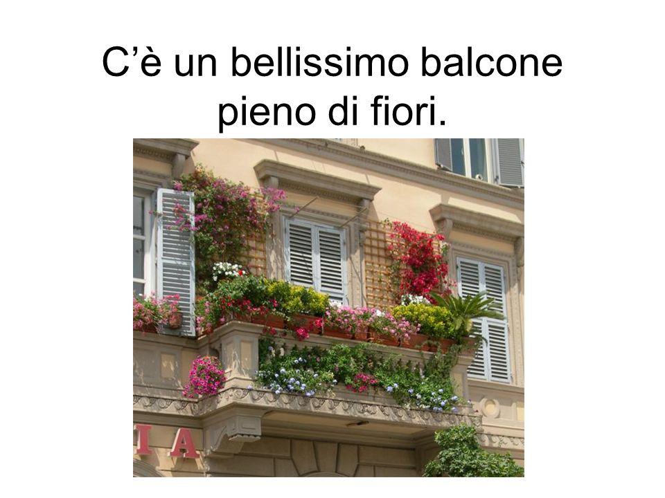 C'è un bellissimo balcone pieno di fiori.