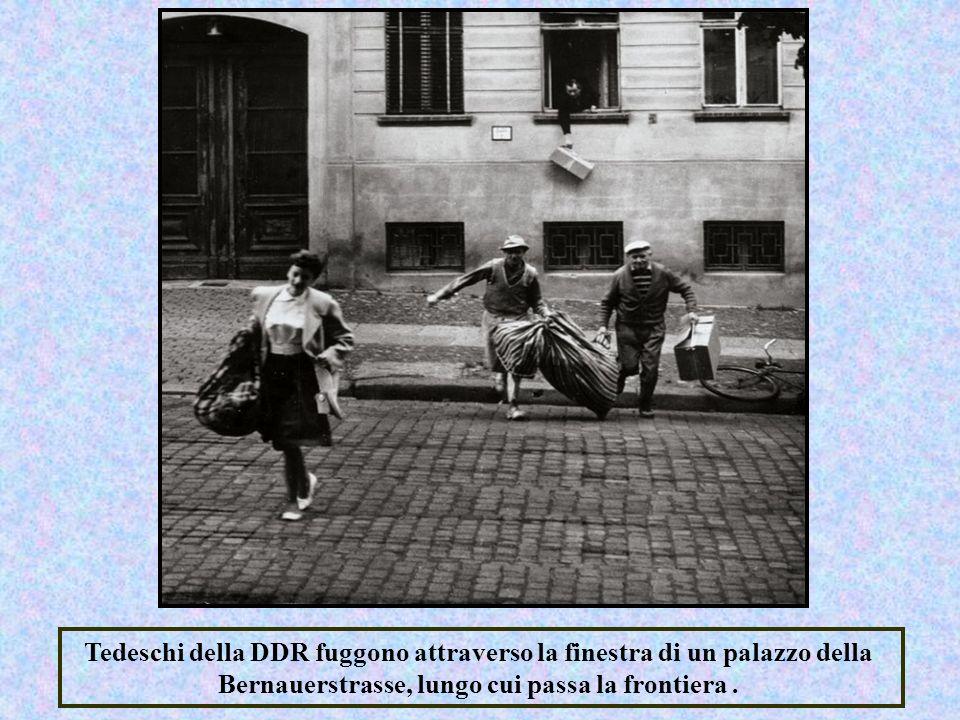 Tedeschi della DDR fuggono attraverso la finestra di un palazzo della Bernauerstrasse, lungo cui passa la frontiera .