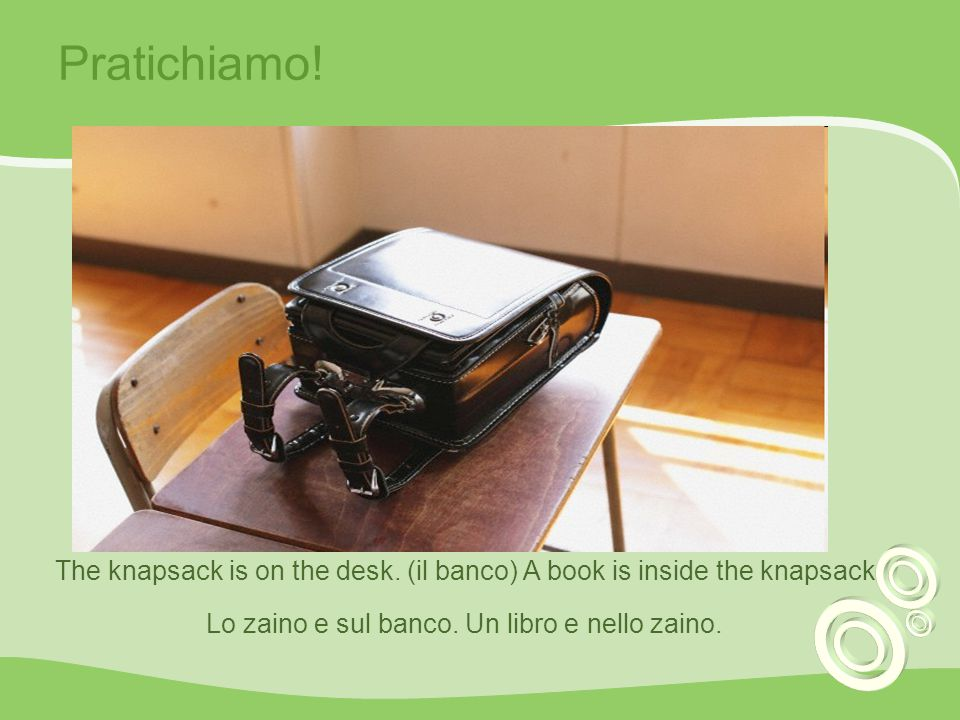 Pratichiamo. The knapsack is on the desk. (il banco) A book is inside the knapsack.