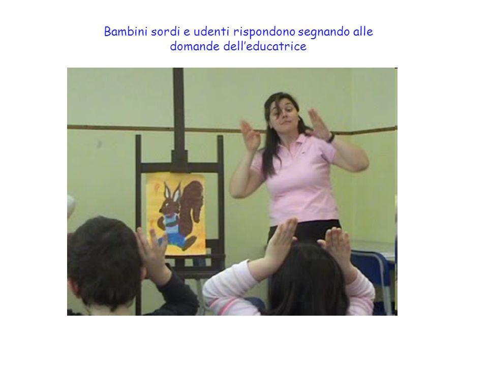 Bambini sordi e udenti rispondono segnando alle domande dell'educatrice