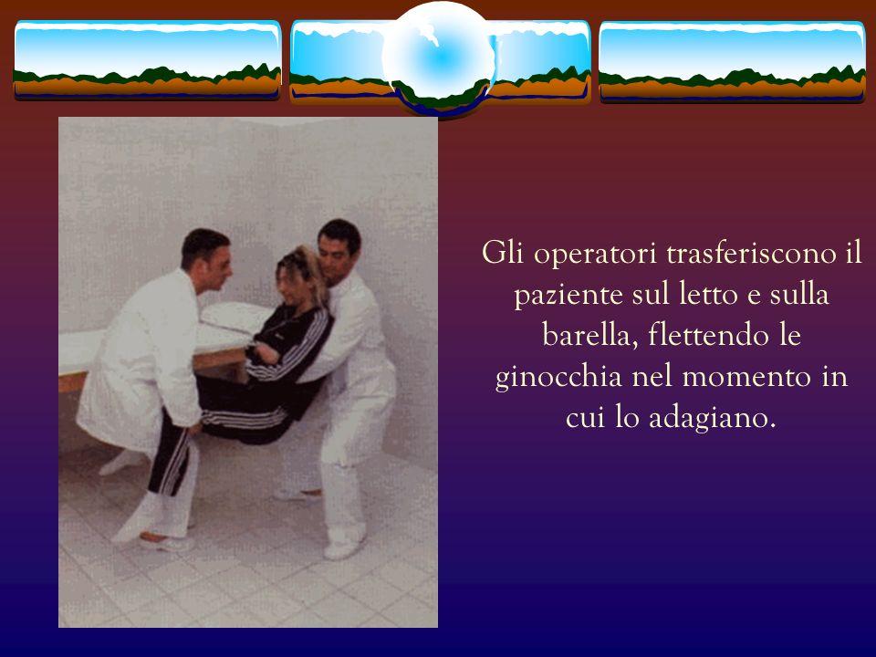 Gli operatori trasferiscono il paziente sul letto e sulla barella, flettendo le ginocchia nel momento in cui lo adagiano.
