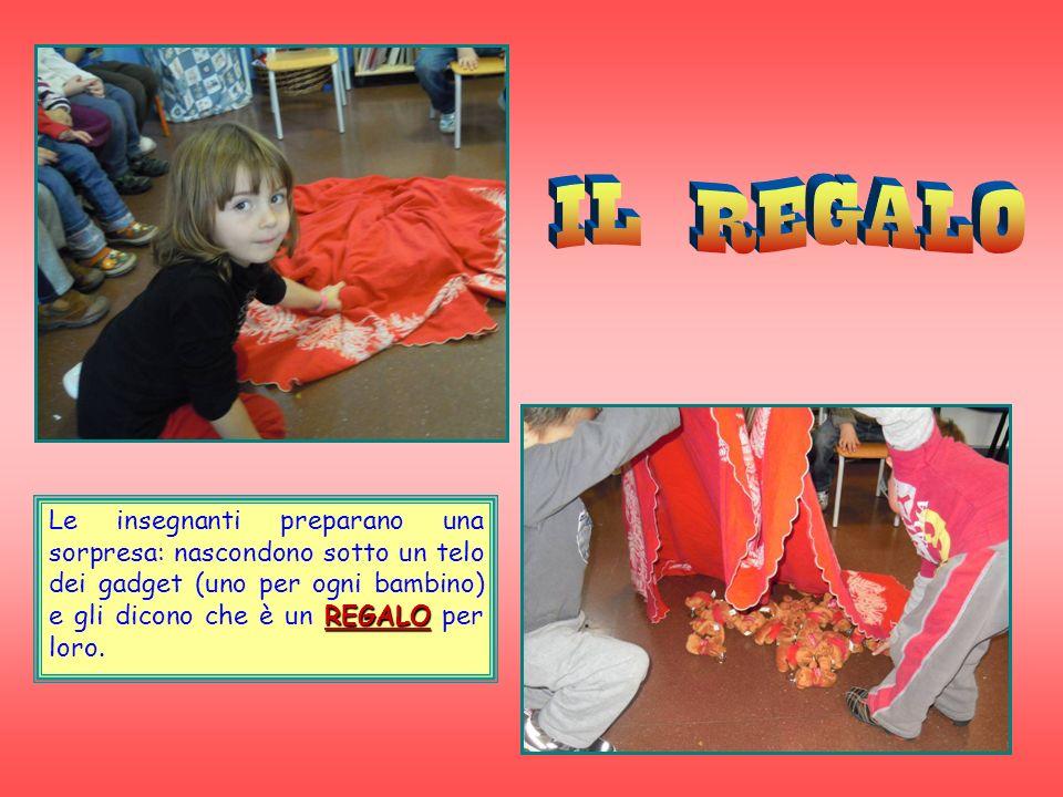 IL REGALO Le insegnanti preparano una sorpresa: nascondono sotto un telo dei gadget (uno per ogni bambino) e gli dicono che è un REGALO per loro.