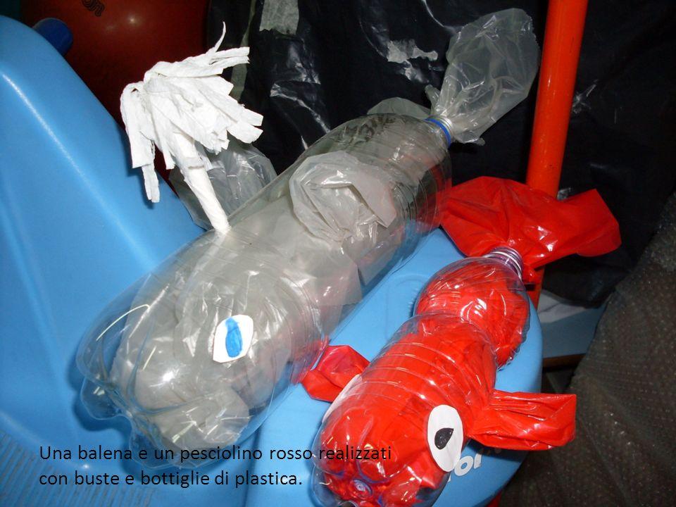 Una balena e un pesciolino rosso realizzati con buste e bottiglie di plastica.