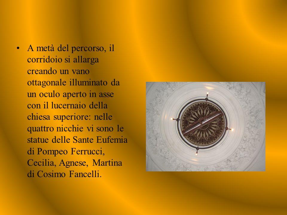 A metà del percorso, il corridoio si allarga creando un vano ottagonale illuminato da un oculo aperto in asse con il lucernaio della chiesa superiore: nelle quattro nicchie vi sono le statue delle Sante Eufemia di Pompeo Ferrucci, Cecilia, Agnese, Martina di Cosimo Fancelli.