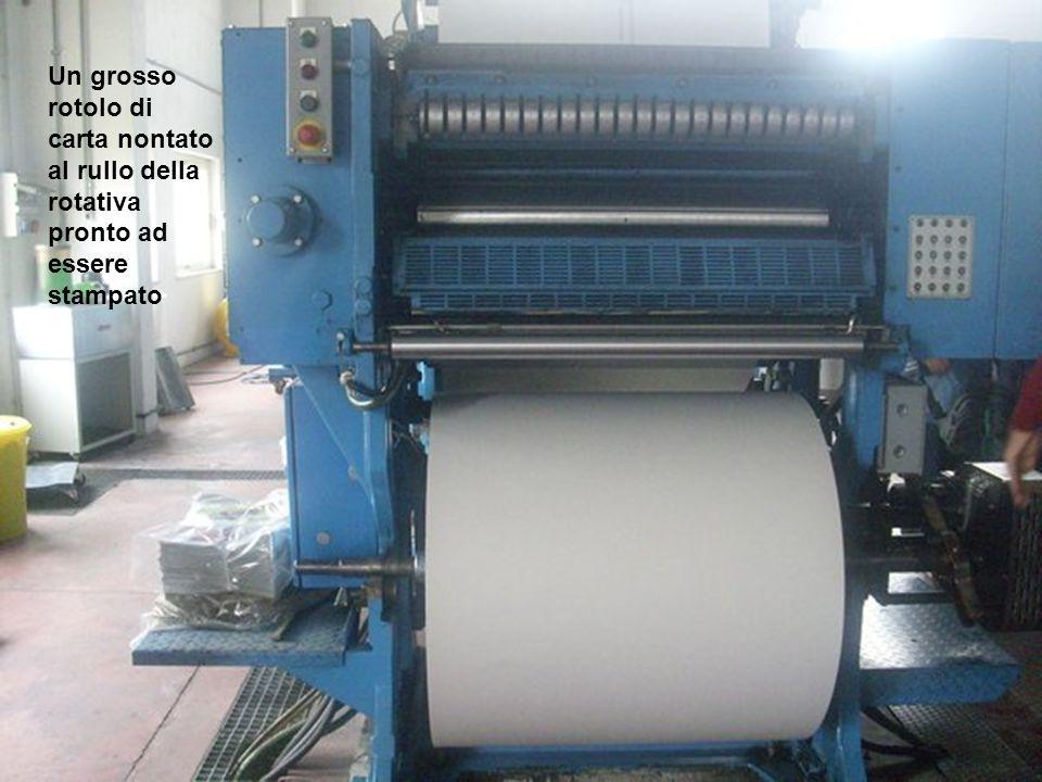 Un grosso rotolo di carta nontato al rullo della rotativa pronto ad essere stampato
