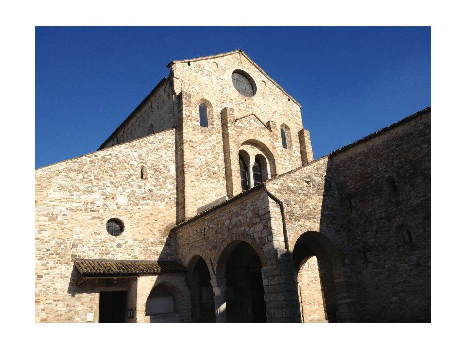 Facciata della basilica e atrio su colonne che costituisce un corpo di raccordo spaziale e liturgico tra la chiesa e il battistero.