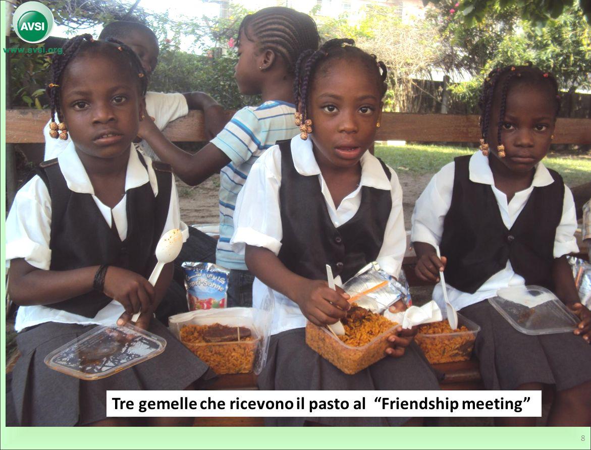 Tre gemelle che ricevono il pasto al Friendship meeting