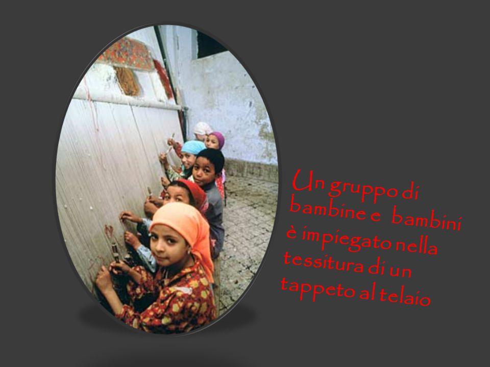 Un gruppo di bambine e bambini è impiegato nella tessitura di un tappeto al telaio