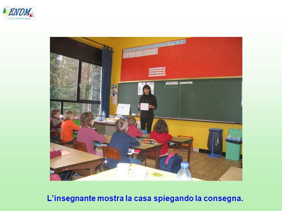 L'insegnante mostra la casa spiegando la consegna.