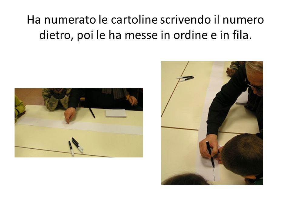 Ha numerato le cartoline scrivendo il numero dietro, poi le ha messe in ordine e in fila.