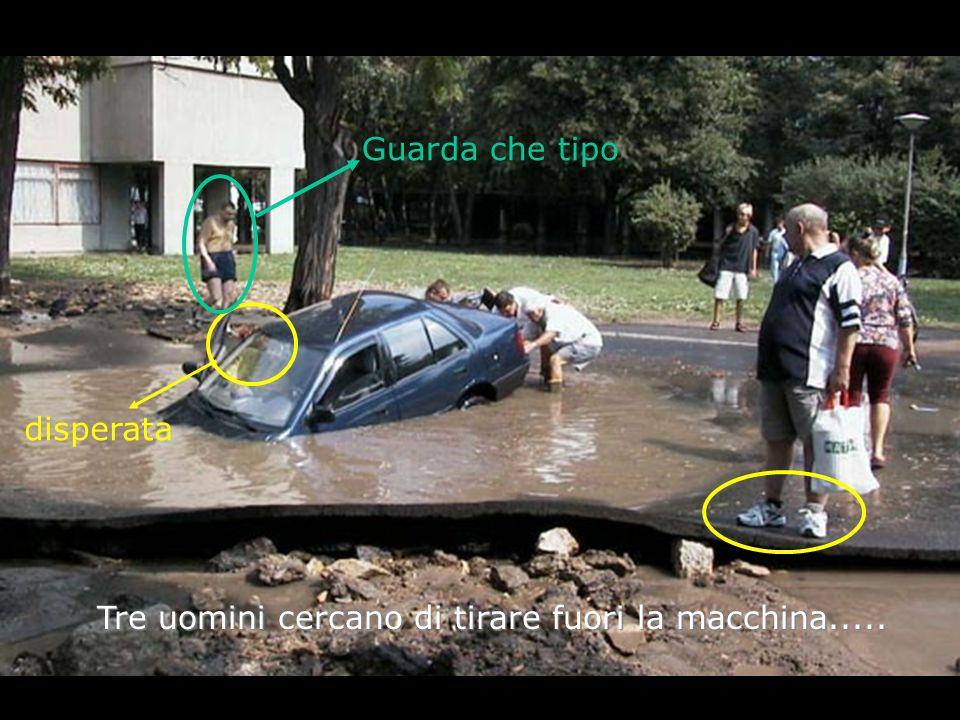 Tre uomini cercano di tirare fuori la macchina.....