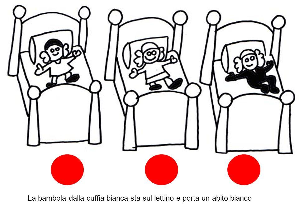 La bambola dalla cuffia bianca sta sul lettino e porta un abito bianco