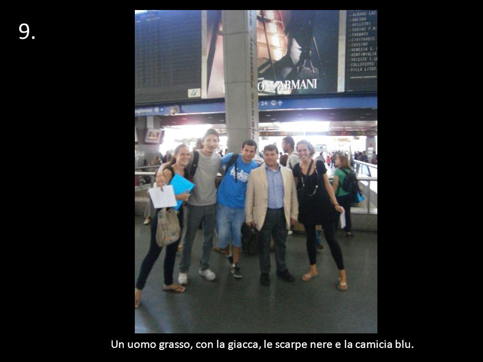9.1 Un uomo grasso, con la giacca, le scarpe nere e la camicia blu.