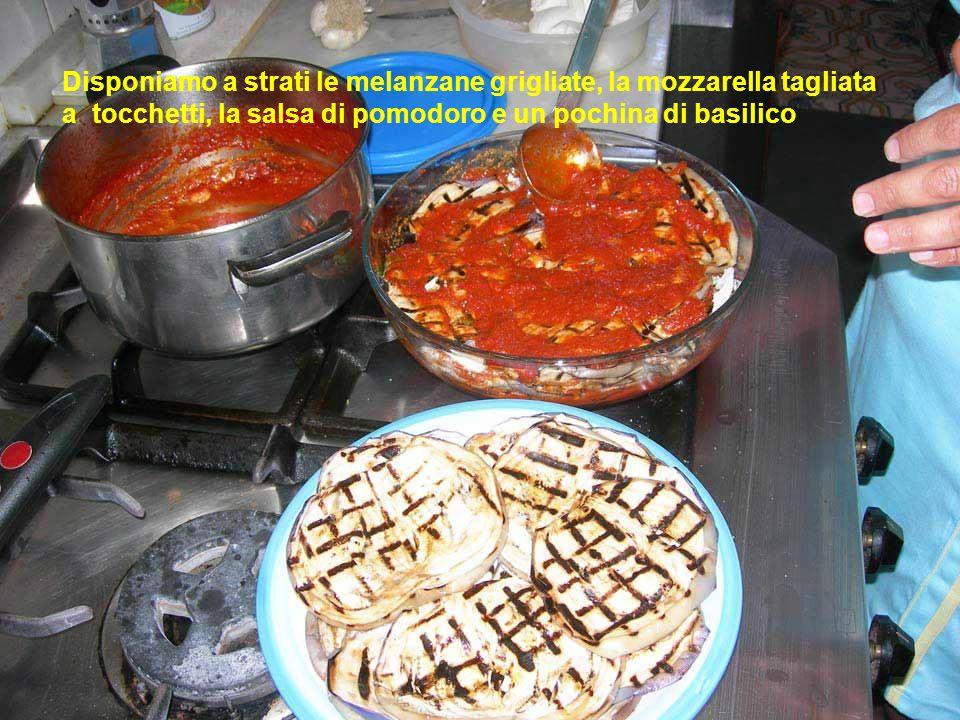 Disponiamo a strati le melanzane grigliate, la mozzarella tagliata a tocchetti, la salsa di pomodoro e un pochina di basilico
