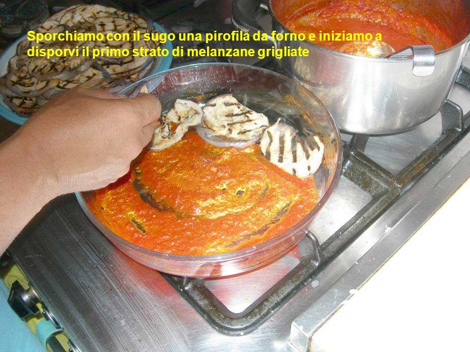 Sporchiamo con il sugo una pirofila da forno e iniziamo a disporvi il primo strato di melanzane grigliate