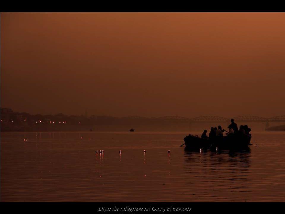 Diyas che galleggiano sul Gange al tramonto