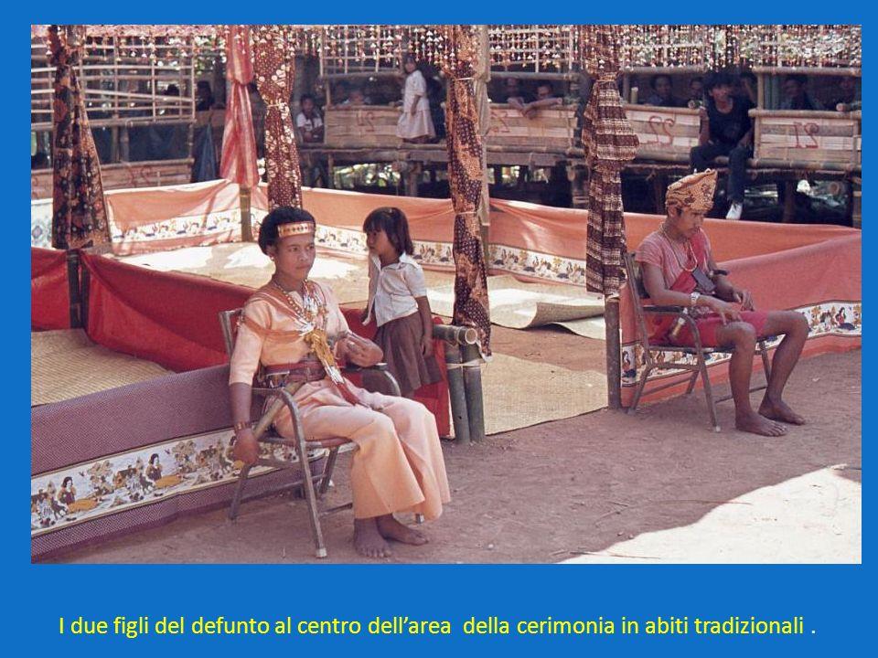 I due figli del defunto al centro dell'area della cerimonia in abiti tradizionali .