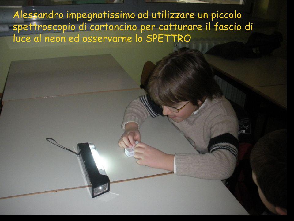 Alessandro impegnatissimo ad utilizzare un piccolo spettroscopio di cartoncino per catturare il fascio di luce al neon ed osservarne lo SPETTRO
